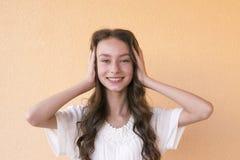 Dam i stängande öron för vit klänning med händer arkivfoto
