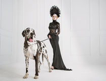 Dam i svart med en vänlig hund royaltyfria bilder