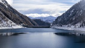 Dam in the italian alps. An artificial lake in the italian alps in a winter day Stock Photos