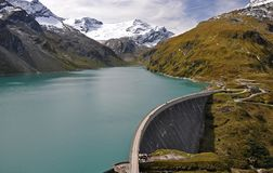 Concrete dam of Mooserboden in Hohe Tauern. Dam lake Mooserboden the snowy peaks of the Hohe Tauern Royalty Free Stock Photo