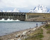 Dam by lake with snowy mountains at national park. Gorgeous view of snowy mountains peeking over Jackson Lake Dam at Grand Teton National Park in Wyoming Stock Photography