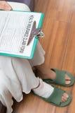 Dam med en hurted fot omkring som fyller en sjukförsäkringreklamationsform arkivbilder
