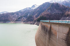 Dam between mountains with green lake at Kurobe dam  japan Royalty Free Stock Photos