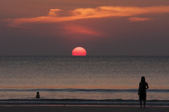 Dam och pojke som tycker om härlig solnedgång på stranden för ferietid, kontursolnedgång på havet Royaltyfri Bild