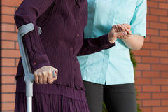 Dam på kryckor och sjuksköterska utanför huset Arkivbilder