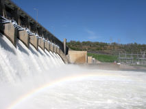 Dam with rainbow. Rainbow across flowing waters of dam royalty free stock photo