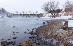 Dam on the river in wintertime unfrozen water snow and ice, frosty day half-steam from the water Stock Photo