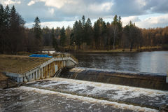 A dam on a small river and a pond with wooded island near Moscow Royalty Free Stock Photos