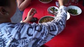 Dam som äter maminudelsoppa längs trottoaren av en stadgata stock video