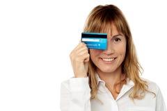 Dam som döljer hans öga med kreditkorten Arkivbild