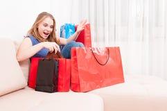 Dam som förbluffas finna saker i shoppingpåsar Arkivfoto