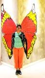 Dam som framme poserar av en väggkonst som visas som fjäril med Royaltyfria Foton