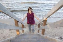 Dam som går upp trappa vid stranden Arkivbilder