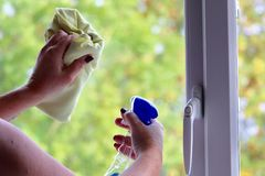 Dam som gör ren fönstren i ett modernt hus royaltyfri fotografi