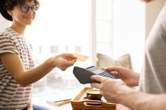 Dam som ger kreditkorten till kassörskan arkivbilder