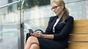 Dam som pratar på smartphonen och att sitta på bänk och den väntande på taxien, grej stock video