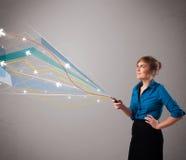 Dam som rymmer en telefon med färgrika abstrakta linjer Royaltyfria Bilder