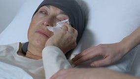 Dam som stöttar gråta den gamla damen som lider cancer som ligger i säng, ingen hoppförbättring stock video