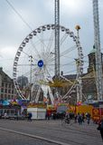 Dam square in Amsterdam with ferris wheel of amusement luna park in centre. The Netherlands, October 12, 2017 royalty free stock photo