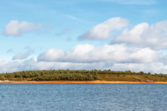 Dam of Valtabuyo. Reservoir of Tabuyo del Monte, pine forest and blue sky with clouds. Royalty Free Stock Images