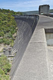 Dam Wall Portrait. Portrait view of dam wall, down to pumping equipment at base. The tower at the base mirrors the tower on top Royalty Free Stock Photos