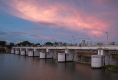 Dam water gate at sunset Stock Image