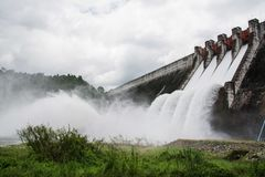 Dam water release. Water spills over the top of dam stock photos