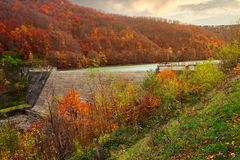 Dam of water reservoir on the Tereblya river. Of Transcarpathia, Ukraine. beautiful autumn scenery with forest in red foliage stock image