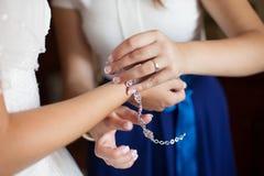 Dama de honor elegante hermosa que pone en la pulsera en la novia Fotografía de archivo libre de regalías