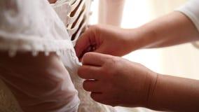 Dama de honor que abotona el vestido en el hogar del ` s de la novia metrajes