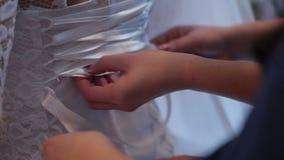 Dama de honor que ata cordones del vestido de boda metrajes