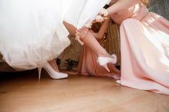 Dama de honor que prepara a la novia para el día de boda la dama de honor le ayuda a llevar una vestir-joyería en su pierna imagen de archivo libre de regalías