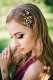 A dama de honra com composição profissional colorida luxuoso e o casamento coroam os acessórios da crista da tiara que estão no fotos de stock royalty free