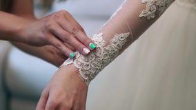 A dama de honra faz o curva-nó na parte de trás do vestido de casamento das noivas vídeos de arquivo