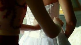A dama de honra faz o curva-nó na parte de trás do vestido de casamento das noivas filme