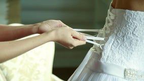A dama de honra faz o curva-nó na parte de trás do vestido de casamento das noivas video estoque