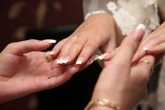 A dama de honra olha o tratamento de mãos da noiva imagens de stock