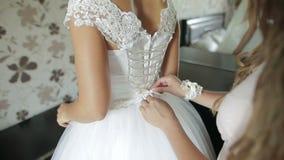 Dama de honra que amarra a curva no vestido de casamento Noiva que prepara-se para a cerimônia de casamento Close-up do vestido d vídeos de arquivo