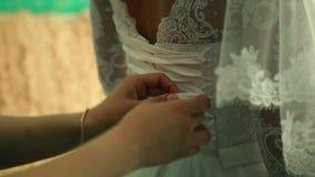 Dama de honra que amarra a curva no vestido de casamento vídeos de arquivo