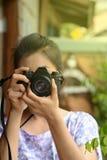 Dama fotograf trzyma retro ekranową kamerę wewnątrz w rocznik sukni Obrazy Royalty Free