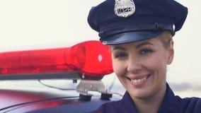 Dama funkcjonariusz policji stoi blisko radiowozu i ono uśmiecha się w nakrętce, prawo ochrona zdjęcie wideo