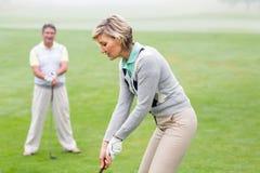 Dama golfista teeing daleko dla dnia oglądającego partnerem Zdjęcie Stock