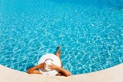 Dama kłaść w błękitne wody z białym kapeluszem Fotografia Stock