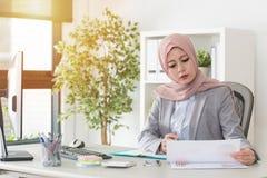 Dama muzułmański urzędnik patrzeje dokument obraz stock