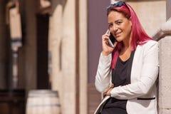 Dama opowiada na telefonie komórkowym przy ulicą obraz stock