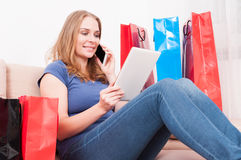 Dama opowiada przy telefonem i robi zakupy online mienie pastylkę Zdjęcie Stock