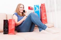 Dama opowiada przy telefonem i robi zakupy online mienie pastylkę Zdjęcie Royalty Free