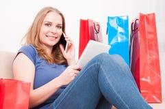 Dama opowiada przy telefonem i robi zakupy online mienie pastylkę Fotografia Royalty Free
