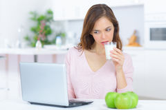 Dama pije szkło dojnego patrzeje laptop Zdjęcia Royalty Free