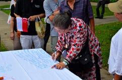 Dama podpisuje petycję przy Maja dnia wiecem Singapur Zdjęcia Royalty Free